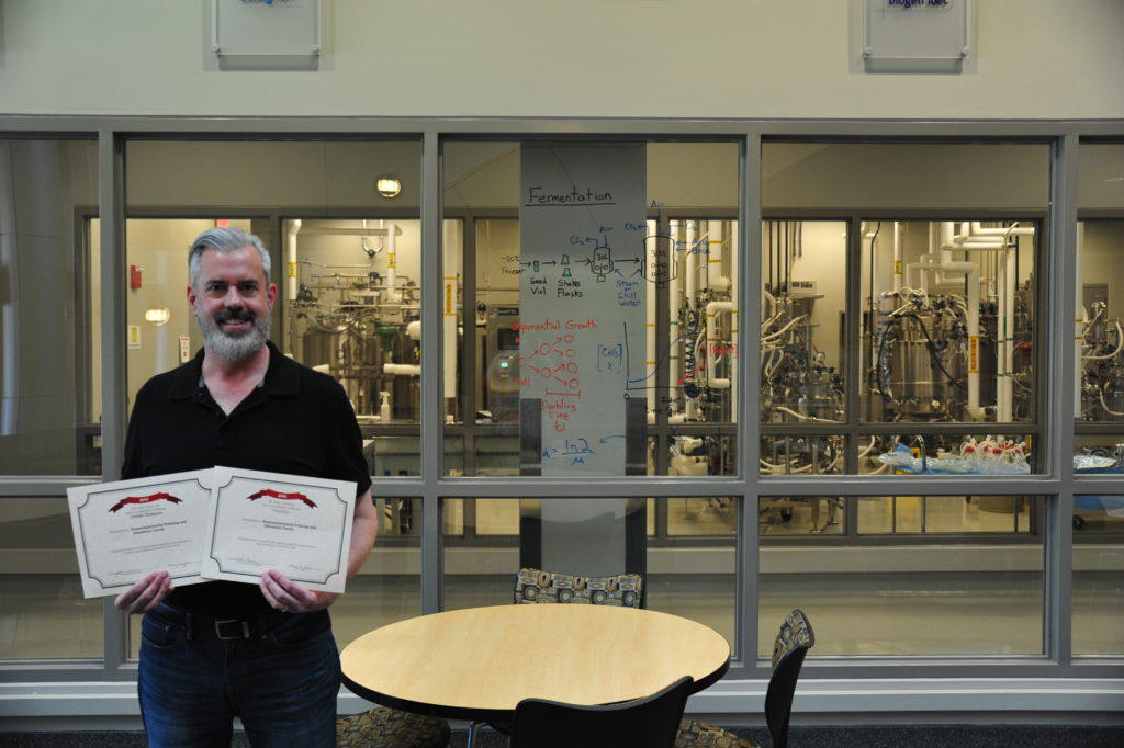 Brian Herring holds his web accessibility challenge certificate inside the lobby of BTEC.