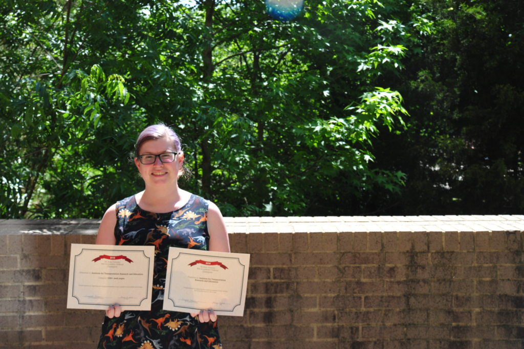 Devin Cremins holds her web accessibility challenge certificate outside on campus.