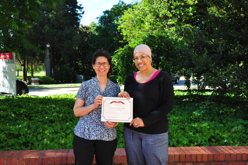 Elizabeth Snively and Jacqueline Perry hold their web accessibility challenge certificate outside on campus.