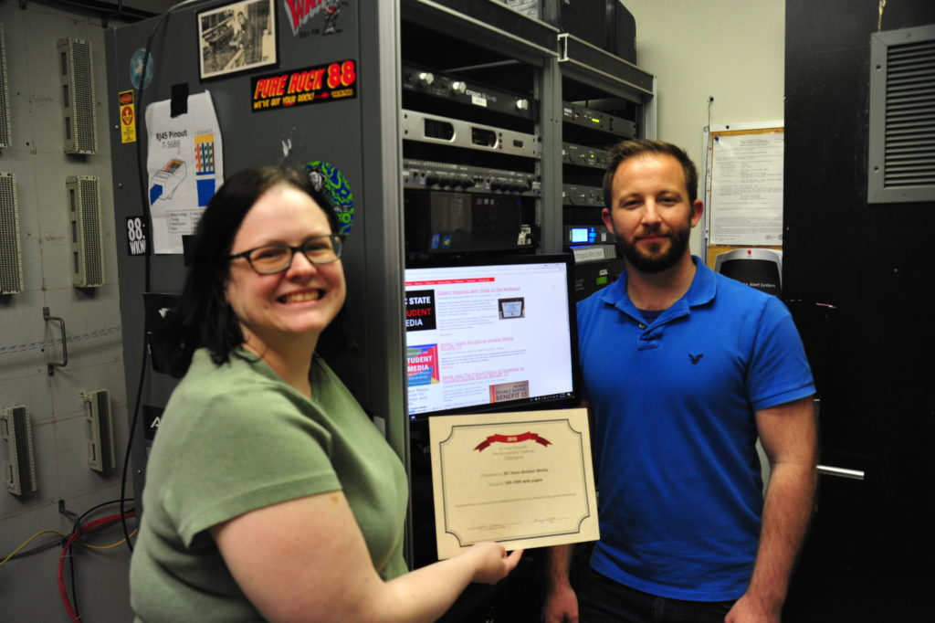Jamie Gilbert and Doug Flowers hold their web accessibility challenge certificate at the NC State radio station.