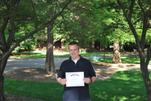 Grae Desmond holding his Web Accessibility Challenge Winner Certificate